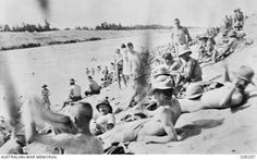 Australian soldiers swimming in and sunbathing beside the Suez Canal.
