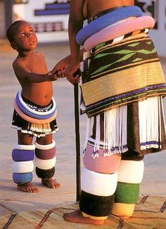 This young Ndebele girl wears bead rolls and a tasseled apron that she will discard when she is initiated into adulthood. The Ndebele people are descended from and related to the Bantu-speakers who spread all over Africa from the area of present day Camer