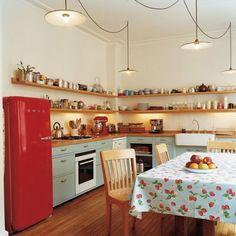Cuisine avec frigo rouge et étagères tout le long des murs