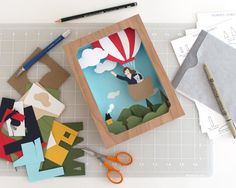 "The Roadside Projects Shadow Box Kit has all the materials you need to create your own three-dimensional cut paper masterpiece. With basic art supplies, you'll learn a fun and unique form of papercraft.    KIT INCLUDES: wood shadow box frame - size: 6"" x 8"" x 2"" satin ribbon for hanging  archival colored card stock + extra for customizing  templates + extra for customizing  transfer paper  easy-to-follow, illustrated instructions    Personalizing your Balloon Adventure shadow box is easy…"