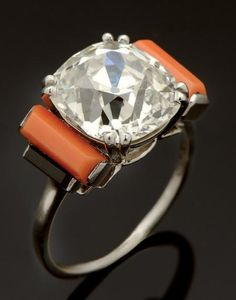 CARTIER Bague en platine ornée d'un diamant coussin taille ancienne calibrant 6,30 cts environ épaulé de gradins sertis de baguettes de corail et de baguettes d'onyx.