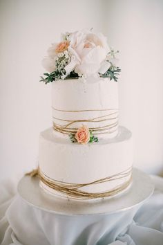 Rustic buttercream wedding cake with twine and roses in white and apricot | Sophie Baker Photography | See more: http://theweddingplaybook.com/light-lovely-intimate-garden-wedding/