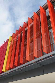 Lâminas de metal coloridas para controlar a luz e sombra na fachada de uma…