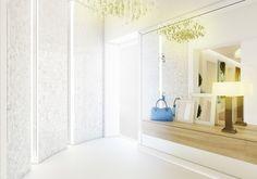 Projekt wnętrza holu wejściowego w apartamencie w Warszawie. W pomieszczeniu królują biele oraz lustra nadając klasyczny, elegancki i reprezentacyjny wygląd.