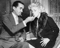 Marilyn Monroe shares a cigarette with Edward R. Murrow during the filming of his television program Person to Person, New York, 1955