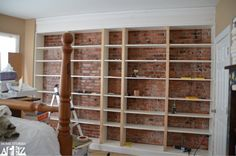 Bookcase over brick. Build soffit first then build out by attaching to the walls and wood frames