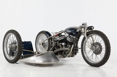 Flathead hardtail custom with racing-style sidecar and curved girder front end