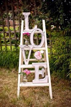 Vintage ladder styled for wedding. Pretty sure this would be easy  cheap to make for random wedding decor. Maybe by the gift or old wedding photo tables. Cheap thrift store ladder, painted. Letters from craft store painted  given a vintage look. Fake flowers in jars.