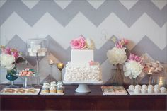 I like that tall glass pedestal with dome, and the use of florals on this table. (The cake itself has too squat a pedestal and the flat trays aren't my favorite)