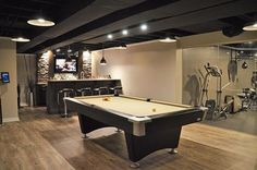 The combination of the black Dryfall ceiling and stone accents behind the bar, this basement has a great modern industrial theme! #basementremodel #basementrenovation #basementreno