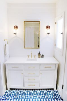 White bath with brass accents and pattered tile floor.