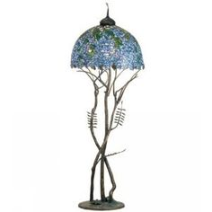 Tiffany Laburnum Floor Lamp. 49879   Features: -Floor lamp. -Cascading blossoms in hues of plum and blue glass with spring green leaves were favored subjects of the l. c. tiffany studio. -Beautiful laburnum stained glass shade with undulating border, is paired with a solid brass base in the form of three bending saplings. -Brass cap and base are finished in an antique patina. Specifications: -Accommodates: (3) 100W medium bulb. -Overall dimensions: 74'' H x 27'' W.