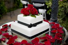 Traditional square two tiered white wedding cake with black satin ribbon. Decorated with fresh red roses.