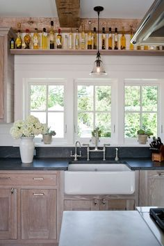 Country kitchen with wire brushed oak kitchen cabinets paired with soapstone countertops and white wood paneling backsplash.