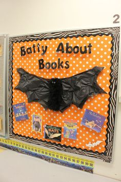 Library Bulletin Board for Halloweem/October ADORABLE.  boa-wrapped paper towel tube body and carefully cut tissue paper wings.