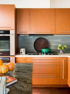 I like the modern cabinets & hardware, and the backsplash. Also when you enlarge this photo you can see how the receptacles are mounted just below the upper cabinets--so I imagine when one is standing in the kitchen they disappear. What a nice idea!