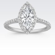 Your chosen marquise diamond will look exquisite with this graceful halo engagement ring.