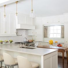 Amazing kitchen features creamy white shaker cabinets adorned with brass knobs paired with light grey quartzite countertops and a white glazed subway tiled backsplash.