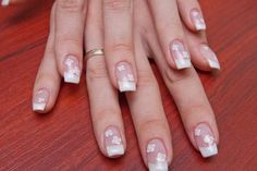 French manicure with white flowers; Copyright Natkin at Dreamstime.com