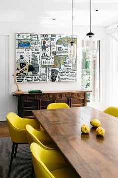 Eclectic yellow dining room decor with modern art, antique buffet
