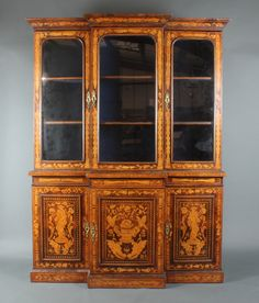 """Lot 1267, A 19th Century Dutch inlaid marquetry breakfront cabinet on cabinet, the upper section with moulded cornice above cupboards fitted adjustable shelves enclosed by panelled doors, the base fitted cupboards enclosed by inlaid panelled doors 81""""h x 60""""w x 16""""d, est  £700-900"""