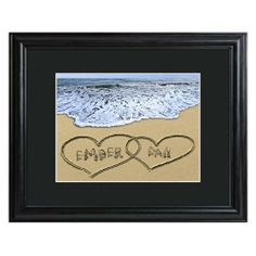 """""""Two Hearts in the Sand"""" Personalized Wall Art features a wood frame.  The print features the sandy shore with a wave coming in from the top. Two hearts are drawn in the sand that overlap. You can personalize these hearts with a name in each."""