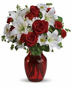 Add some romance with this rich #arrangement of luxurious #flowers in classic Valentine's colors. Red #roses, white lilies and playful daisies are gathered in a ruby red #vase!