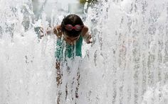 A girl cools off in the water fountains at Yards Park along the Anacostia River in SE Washington July 3, 2012.