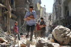 Deuxième prix catégorie Spot News. Rescapés des décombres. Des Syriens éloignent des bébés de la zone de bombardement dans le quartier de Salihin, tenu par les rebelles, à Alep, le 11 septembre 2016.  PHOTO AMEER ALHALBI / AFP
