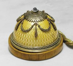 A JEWELED SILVER-GILT AND GUILLOCHÉ ENAMEL BELL-PUSH   MARKED FABERGÉ, WITH THE WORKMASTER'S MARK OF VICTOR AARNE, ST. PETERSBURG, 1899-1904, SCRATCHED INVENTORY NUMBER 4205  Hemispherical, on a circular wood base, the body enameled in translucent yellow over a wavy guilloché ground, centering a moonstone cabochon push-piece within a stiff-leaf border, suspending a band of tied laurel swags, the base with beaded border, marked on upper mount