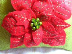 Green burlap pillow with red poinsettia embroidered by betsstuff
