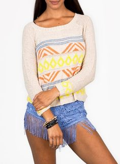 Cozy on up and get stylish with this long sleeve, slightly stretchy sweater featuring a brightly hued Aztec print.