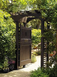 Black paint and brass  numbers give this Dutch door and its sturdy arbour,  a formal elegance.  The full or half door option can either usher guests to the diminutive  patio beyond or shield the garden from the nearby street. Things I love!!!
