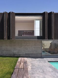 Folding sun screen with linear bench adjacent to lap pool -- concrete and landscape divider