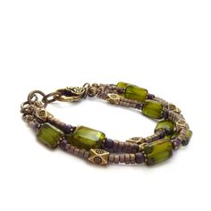 Triple-strand bohemian bracelet. I used Czech glass rectangle beads in an exceptional shade of olive green and added small metallic seed bead cubes that have a wonderful shimmer. Detailed bronze spacer beads compliment the colors and a chunky bronze lobster clasp ties it all
