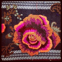 """A detailed tapestry of a rose in vibrant pink and orange on a dark background with brown and green leaves. """"Tapestry rose detail #embroidery #rose"""" As snapped by Matthew Williamson on Instagram."""