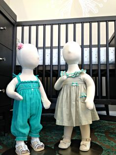 2014 Spring/Summer Kids Apparel Collection.  Left mannequin: Tartine et Chocolat teal romper with white stitching and bow detailing paired with Mayoral white sandals with braided straps and flower detail.  Right mannequin: Tartine et Chocolat beige dress with teal bow and ruffle detail, paired with Tartine et Chocolat beige and white flats with scalloped ankle strap.