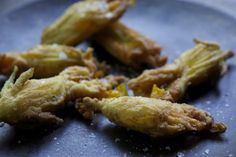Zucchini blossoms: stuff the flowers with fresh ricotta and herbs, roll them in egg, dredge them in flour, and fry them in neutral oil until they're crisp and golden. Sprinkle with flaky sea salt for extra crunch, and serve hot