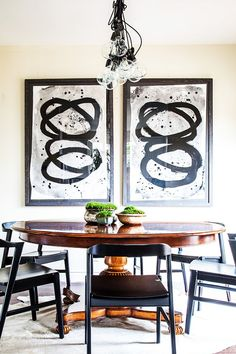 Dining area with round table, exposed bulb chandelier, and large artwork