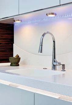 Beautiful blue LED lighting brightens up this slick white kitchen.