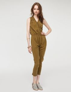 Sleeveless jumpsuit from Black Crane. Features oversized styling, criss cross neck, elastic waist, two side welt pockets, side cutout detail, and elastic banding at leg openings.