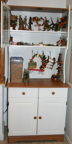This is where I keep all of my parrot's toys, food and supplies. I used a microwave stand... I used 3mm hooks and hung all the toys. Food in the middle.   And bags of food and treats below, as well as dishes and other stuff.  Works so well for having it all in one place.