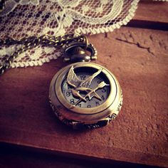 1 Pc Small Pocket Watch Necklace with Hunger Games Mocking Jay Pin Face Vintage Style Victorian Engravings Pocketwatch CHAIN INCLUDED. $8.00, via Etsy.