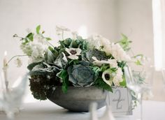 This moody centerpiece made of succulents, anemones, roses, air plants and more add depth and beauty to any tabletop!