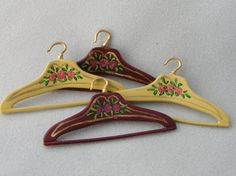 A set of four hand-painted miniature coat hangers, two in dark red and two in a soft creamy yellow. (buttermilk) Painted by myself on British made metal miniatures. Each hanger measures 3.75cm wide. These are collectors items and are not suitable for children.
