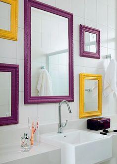 De vários tamanhos, as molduras de quadro pintadas de roxo e amarelo com espelho dão a sensação de amplitude em vários pontos.