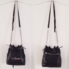 """Guess Drawstring Cross Body Bag Guess  Drawstring Cross Body Bag  ·         Black ·         Faux leather ·         Crocodile print ·         Silver hardware ·         Magnetic snap closure ·         Zipper pocket on back ·         Interior zipper pocket ·         3 interior slide pockets ·         Measures 13.5""""x5""""x10"""" ·         Strap 25"""" Guess Bags Crossbody Bags"""