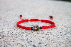 Náramek s buddhou Náramek drhaný z červené nylonové šňůrky, kovové hlavy buddhy a větších černých rokajlových korálků. Konce šňůrek jsou ozdobeny černými dřevěnými korálky. Velikost náramku je cca 18 cm, dá se upravit pomocí uzlíkového zakončení.