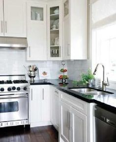White cabinets, dark counters, stainless steel and dark wood floors= my dream kitchen.