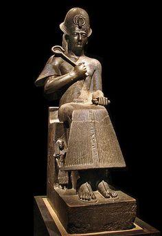 Ramsés II: 1380 a.C.,  XIX Din, Imperio Nuevo, 190 cm, Diorita, Museo Egipcio de Turín. Corona esférica con alerones laterales, y en la frente, envuelta en sus anillos, la cobra que protege al rey de sus enemigos. En las manos aparecen los símbolos del poder político: con la derecha acerca a su pecho el cetro, y con la izquierda apoyada en una pierna estrecha un pequeño cilindro que sustituye al otro cetro real. La larga túnica plisada de lino blanco, es un traje ceremonial de sumo…